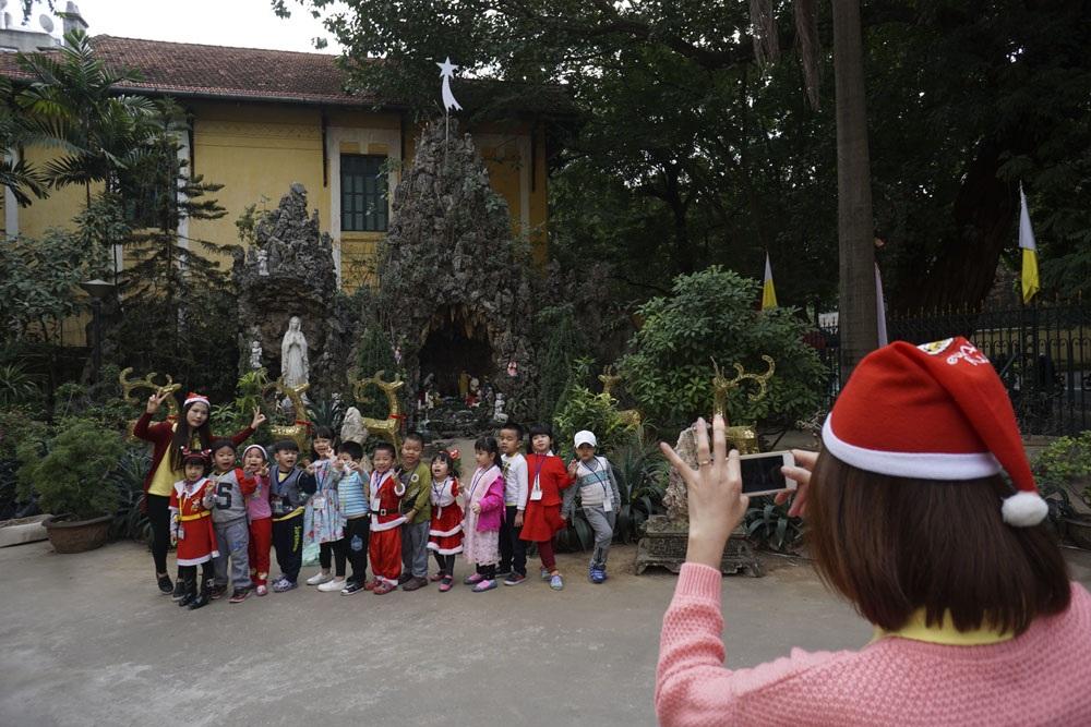 Các em nhỏ trong trang phục ông già Noel chụp ảnh lưu niệm trước hang đá - nơi chúa giáng sinh - tại sân nhà thờ Cửa Bắc.