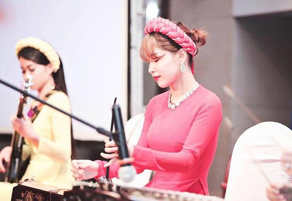 Hình ảnh Thùy Linh chơi đàn bầu ở một buổi biểu diễn âm nhạc dân tộc.