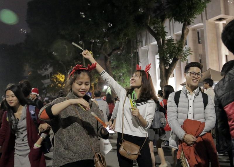 Các cô gái hóa trang tinh nghịch với bờm tuần lộc, phấn khích đùa nghịch, chụp ảnh giữa dòng người dạo chơi lễ Giáng sinh