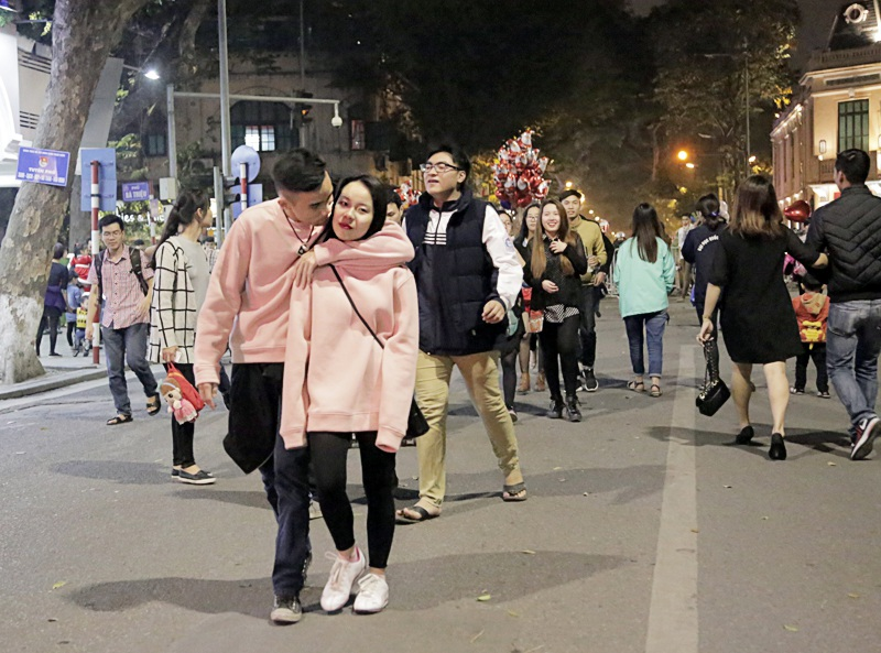 Hai bạn trẻ diện đồ đôi, trao nhau những cử chỉ tình cảm trên phố đi bộ