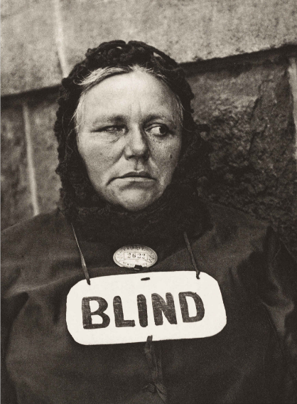 """Bức ảnh """"Người mù"""" do Paul Strand chụp năm 1916. Nhiếp ảnh gia Strand là người đi tiên phong cho loại hình nhiếp ảnh tư liệu hoàn toàn mới có tên gọi là nhiếp ảnh đường phố. Ông sử dụng một ống kính giả để đánh lạc hướng nhân vật ông định chụp, trong khi vẫn đặt máy ảnh ở một góc độ khác mà nhân vật không hề biết. Mục đích của việc làm này là nhằm cho ra đời những bức ảnh chân thực nhất của người đối diện thay vì đi theo phong cách chụp ảnh """"diễn sẵn"""" thông thường. Đó là lý do vì sao gương mặt và ánh mắt của người phụ nữ mù lại quay về hướng khác trong bức ảnh trên."""