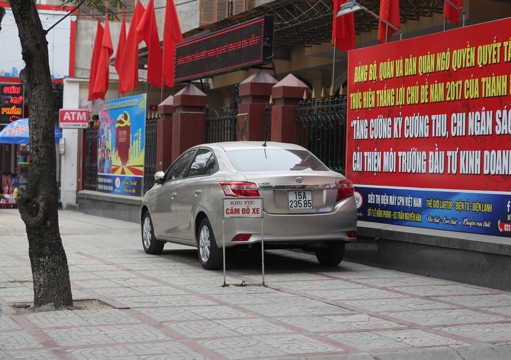 Trước cổng một cơ quan nhà nước của Hài Phòng, một chiếc xe ô tô đậu trên vỉa hè, ngay trước tấm biển báo khu vực cấm đỗ xe