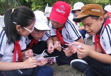 Học trò khối lớp 4 cùng trao đổi về bài tập Toán trong giờ học ngoài trời.