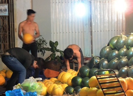 Đối diện với chỗ anh Minh, một nhóm thanh niên đang kiểm lại hàng dưa.
