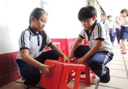 Một nhóm học sinh khác có nhiệm vụ dọn bàn ghế.