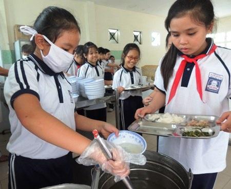 Em Vũ Ngân Anh (bên trái) tham gia công việc chia đồ ăn cho bạn.