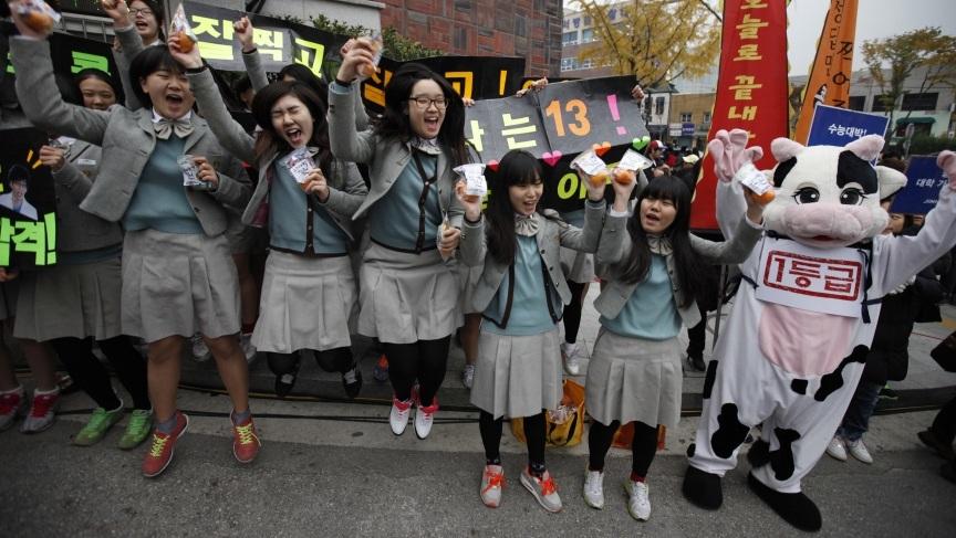 Các em học sinh nhỏ tuổi cổ vũ cho các anh chị thi tốt (Ảnh AFP)