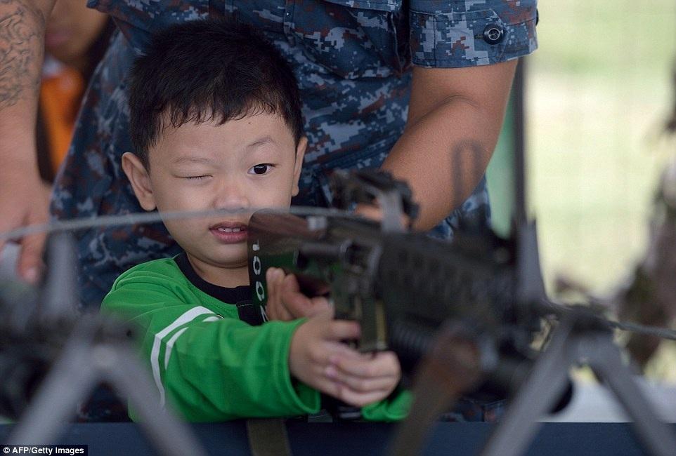 Một sỹ quan tại doanh trại hải quân đang hướng dẫn cậu bé ngắm bắn