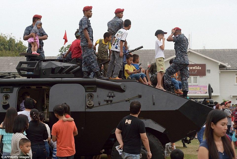 Các cô bé, cậu bé đang ngồi trên chiếc xe tăng bọc sắt để tìm hiểu về loại xe này
