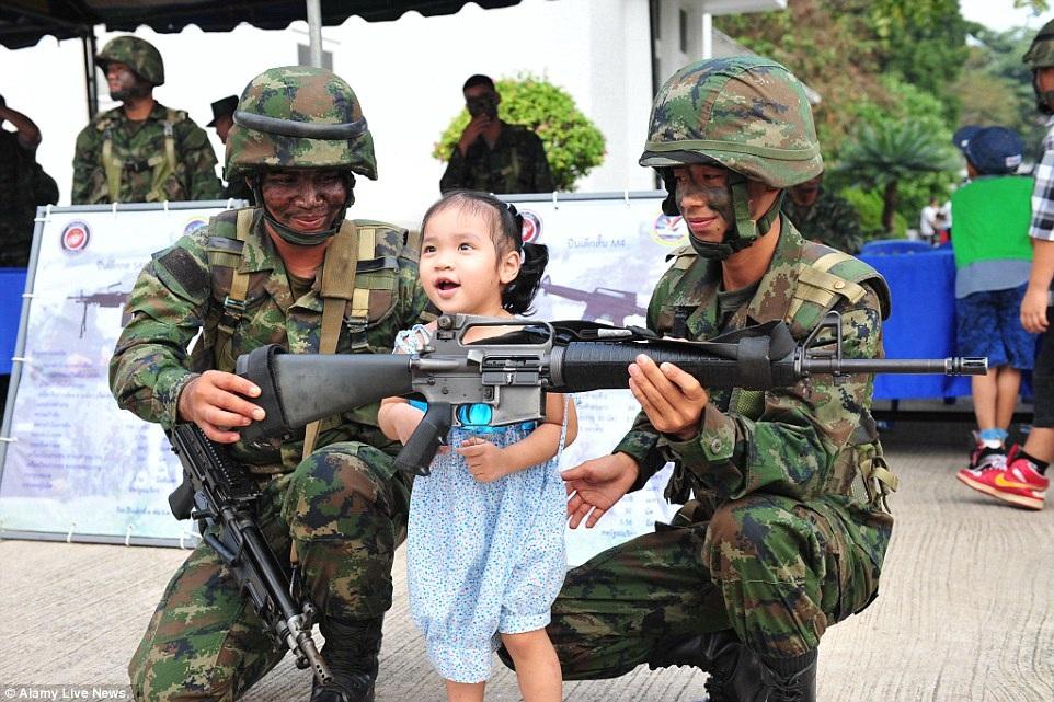 Bé gái tỏ ra rất thích thú khi lần đầu tiên được chạm vào khẩu súng thậm chí còn to cả mình