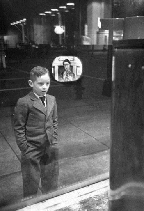 Một cậu bé tranh thủ đứng xem chương trình truyền hình từ một chiếc TV đặt trong cửa hiệu. Ảnh chụp năm 1948.