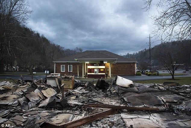 Một căn nhà ở thành phố Gatlinburg, bang Tennessee, đã may mắn thoát khỏi lưỡi lửa, trong khi ngay đối diện là một căn nhà khác không được may mắn như vậy, đã nằm gọn trong quầng lửa thiêu rụi.