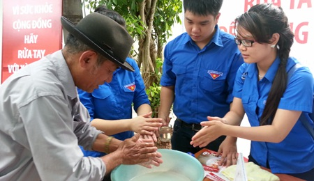 Các tình nguyện viên hướng dẫn người dân sử dụng xà bông trước khi vệ sinh cá nhân.