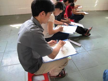 Thí sinh thi khố H chăm chú cho bức vẽ của mình.