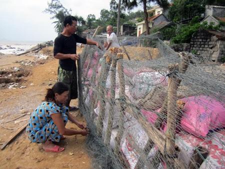 Nhiều nhà tự mua lưới thép, đóng cát để xây thành chờ bão.