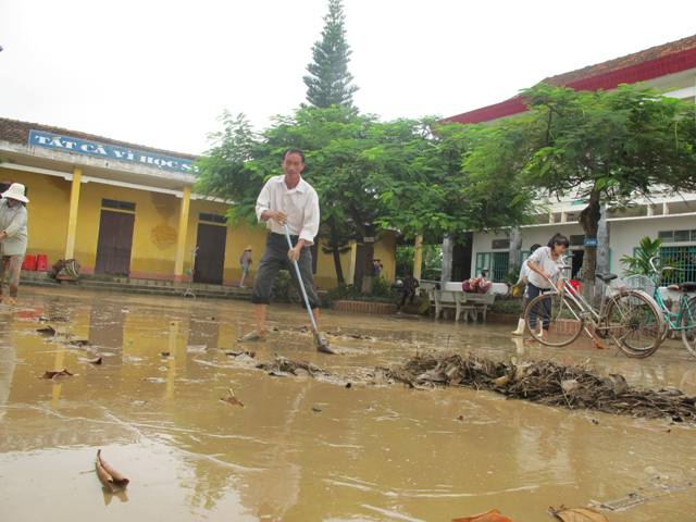 Thầy Văn Huy Tiến - hiệu trưởng trường tiểu học Quỳnh Dị cũng xắn quần lội bùn dọn dẹp.