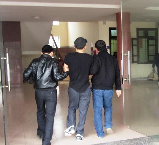 """Thắng Ký"""" (giữa) bị áp giải trên xe vào trụ sở CQĐT Công an Nghệ An."""