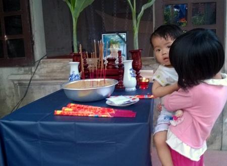Cháu Quỳnh Chi bế em 18 tháng tuổi bên bàn thờ mẹ.