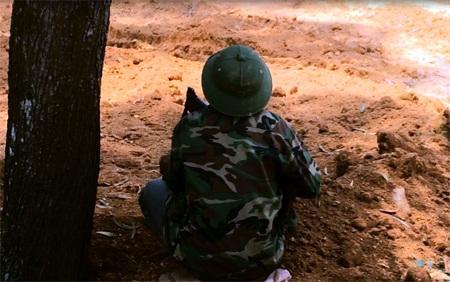 Tay súng tay lăm le súng nấp dưới gốc cây dõi theo đàn chim trú ngụ trên tán cây