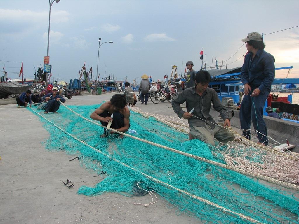 Ngư dân chuẩn bị lưới trước khi vươn khơi