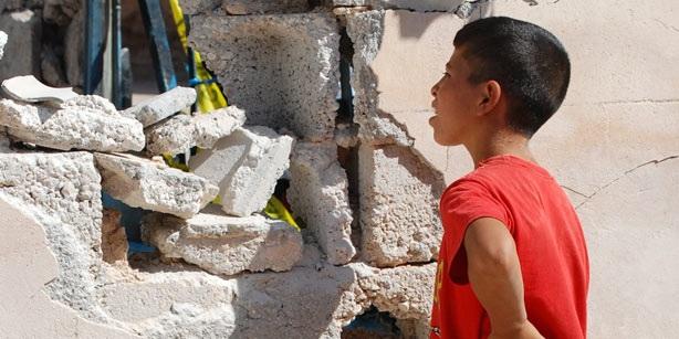 Một cậu bé Thổ Nhĩ Kỳ cố nhìn vào bên trong căn nhà đổ nát do trúng đạn pháo từ Syria.