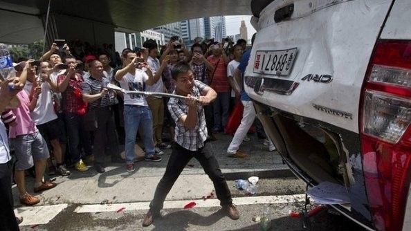 Một người biểu tình Trung Quốc đập phá một xe ô tô của Nhật Bản trên đường phố Bắc Kinh.