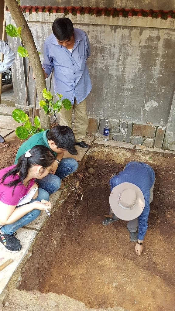 PGS.TS. Bùi Văn Liêm, Phó Viện trưởng Viện Khảo cổ học (đứng) quan sát kỹ lớp đất lạ vừa đào được