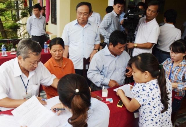 Ông Nguyễn Văn Cao, Chủ tịch UBND tỉnh Thừa Thiên Huế (đứng, đeo kính) đi kiểm tra công tác chi trả tiền bồi thường sự cố Formosa cho người dân (ảnh: Cổng thông tin UBND tỉnh Thừa Thiên Huế)