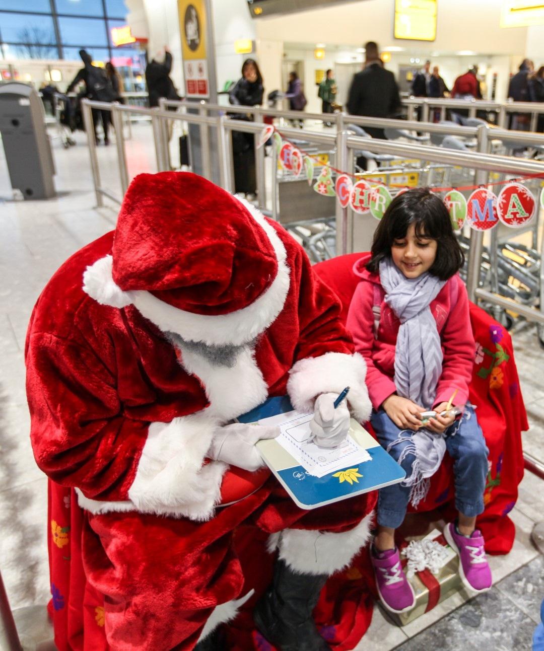 Hành khách nhí chia sẻ điều ước với ông già Noel Vietnam Airlines tại sân bay London Heathrow.