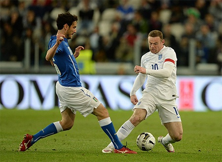 Andrea Ranocchia (trái) tranh bóng cùng Rooney