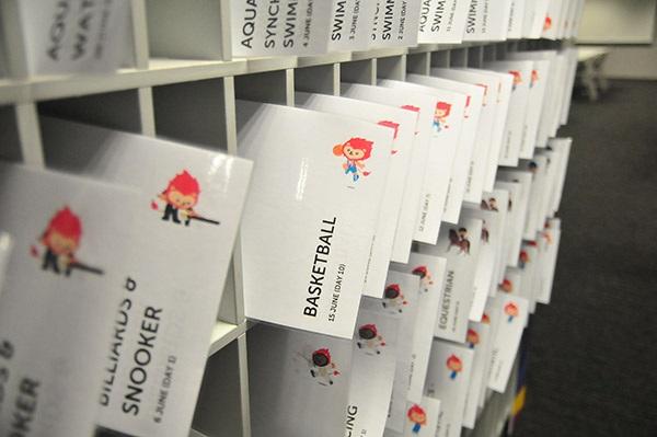 Lịch thi đấu các môn được in và bày theo từng ngăn để phát cho phóng viên