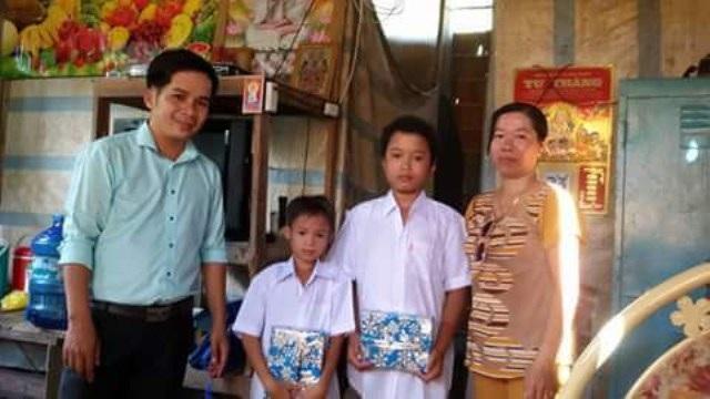 Thầy Nam trao trao sách, vở cho học trò nghèo.
