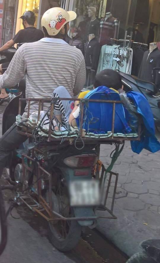 Hình ảnh bé trai vắt vẻo trong khung sắt sau xe máy gây tranh cãi trên cộng đồng mạng (ảnh: vnn)