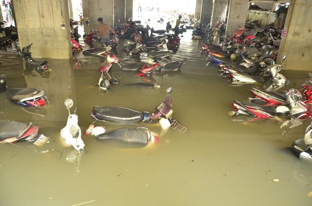 Mưa lớn khiến nhiều tầng hầm để xe ở TP HCM bị ngập lụt, khiến hàng trăm phương tiện chìm trong biển nước. Hầm để xe trên đường Nguyễn Siêu, bị nước nhấn chìm sau trận mưa chiều ngày 26/9, nhưng phải đến ngày 27/9, chủ phương tiện mới đến mò xe máy mang đi sửa chữa. Tầng hầm để xe KTX ĐH Quốc gia TPHCM cũng bị ngập sâu 1,8 mét, nhấn chìm gần 600 xe máy, hơn 250 xe đạp điện, xe đạp. (Ảnh: Đình Thảo)