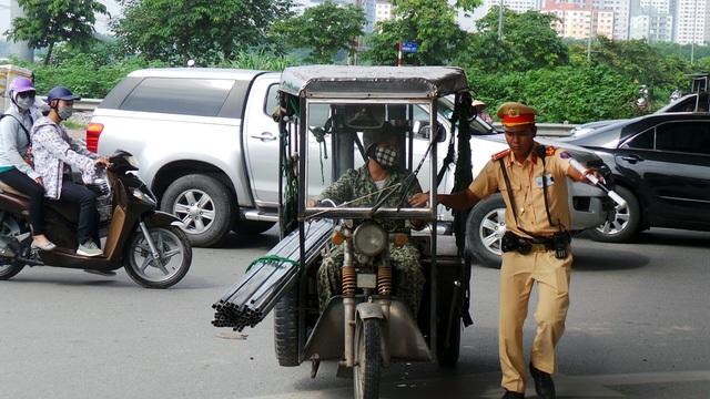 Sau khi một cháu bé tử vong do tấm tôn cứa vào cổ, lực lượng Cảnh sát giao thông CATP Hà Nội đã ra quân truy quét các xe xích lô, xe mô tô chở hàng cồng kềnh, xe ba bánh tự chế, tự gióng... (Ảnh: Mạnh Thắng)