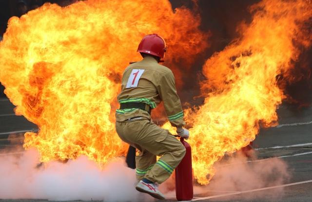 """Lực lượng phòng cháy chữa cháy ở TP HCM """"lao vào biển lửa"""" tại Hội thao Kỹ thuật chữa cháy, nhân Kỷ niệm 55 Ngày truyền thống Lực lượng cảnh sát PCCC 4/10). (Ảnh: Đăng Lê)"""