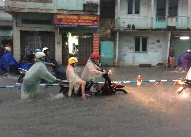 Triều cường dâng cao kết hợp với cơn mưa như trút kéo dài hơn 2 giờ đồng hồ vào chiều tối nay 16/10 khiến hàng loạt tuyến đường tại TPHCM bị ngập sâu, nước cuồn cuộn chảy trên đường, có chỗ nước ngập lút cả xe máy. (Ảnh: Đình Thảo)