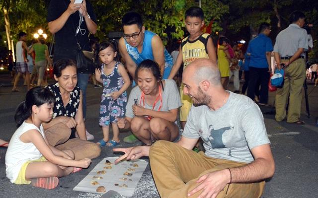 Du khách nước ngoài chơi cùng trẻ em trên phố đi bộ quanh Hồ Gươm