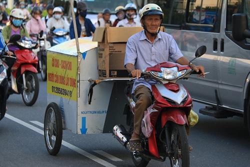 """Hơn 3 tháng nay, nhiều người dân Đà Nẵng đã quen thuộc với hình ảnh ông Nguyễn Công Long (77 tuổi) đi xe máy kéo theo một cái thùng nổi bật với dòng chữ: """"Cũ cho - sạch cho. Người cần dùng lấy dùng"""". Đó là ông đang đi gom quần áo cũ cho những người nghèo. (Ảnh: Khánh Hồng)"""