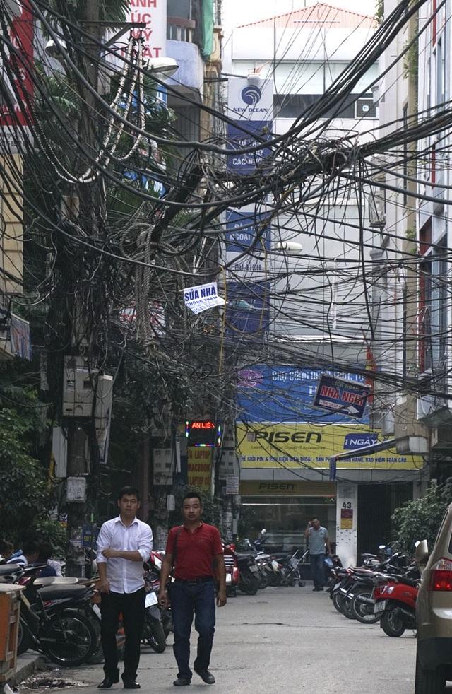 Mạng cáp viễn thông và đường dây điện tại Hà Nội vẫn là một nỗi ám ảnh với người dân Thủ đô. Những bó dây chằng chịt được buộc tạm bợ, chạy vắt vẻo, nhiều chỗ như muốn sà xuống người đi đường vẫn là một hình ảnh đặc sản của Thủ đô. (Ảnh: Hữu Nghị)