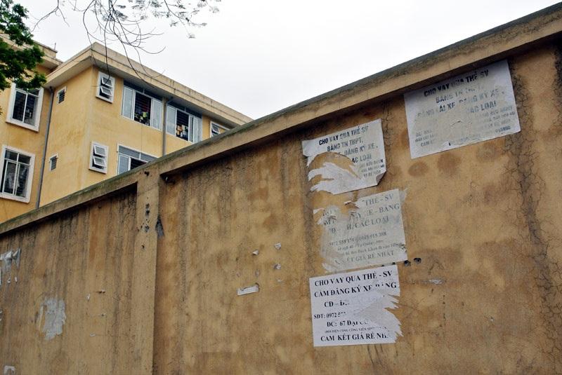 Bờ tường bao quanh ký túc xá ĐH Bách khoa nham nhở những quảng cáo rao vặt tín dụng đen.