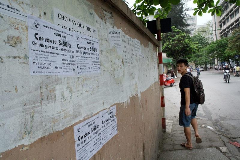 Quảng cáo tín dụng đen dán chồng chéo trên bờ tường trên phố Tạ Quang Bửu, nơi rất đông sinh viên.
