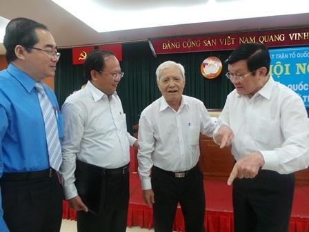 Chủ tịch nước Trương Tấn Sang (phải) trò chuyện cùng bà con cử tri sau buổi tiếp xúc