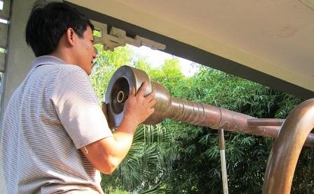 Anh Ngô Văn Hòa, người tham gia sản xuất thổi thử chiếc kèn đồng lớn nhất Việt Nam.