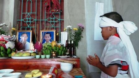 Cháu Trương Văn Thành trước bàn thờ mẹ và chị.