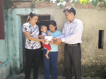 Đại diện chính quyền địa phương trao quà bạn đọc ủng hộ đến gia đình chị Huấn.