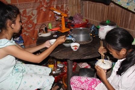 Hai chị em ăn vội bữa cơm trưa để tiếp tục đến lớp.