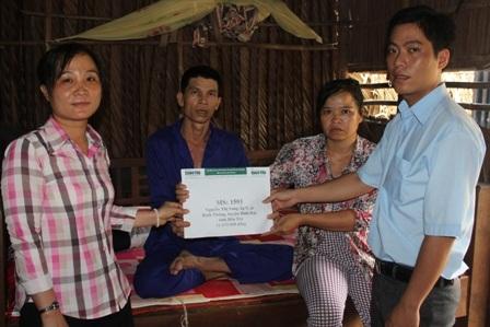 Đại diện Hội Chữ Thập đỏ cùng chính quyền địa phương trao tiền cho gia đình bà Sang