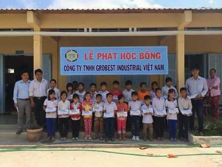 Đại diện công ty Grobest trao học bổng cho học sinh tại trường tiểu học Hòa Minh B (Châu Thành)
