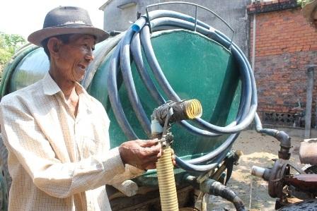 Ông Hưng với chiếc xe công nông, ống dẫn nước và bồn chứa để hành nghề bán nước ngọt